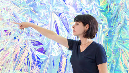 brunette woman points in surprise with her finger against  background of an ice wall. 版權商用圖片