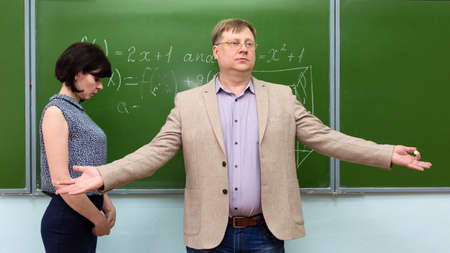 The professor asks the students to help with the answer to the ignorant student at the blackboard. 版權商用圖片