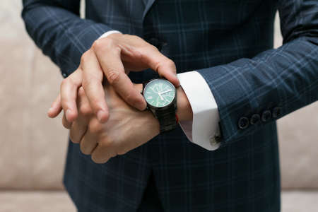 man looks at his wristwatch afraid of being late for date.