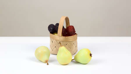 Handmade soap in the form of berries and pears in a wicker basket on a white background.