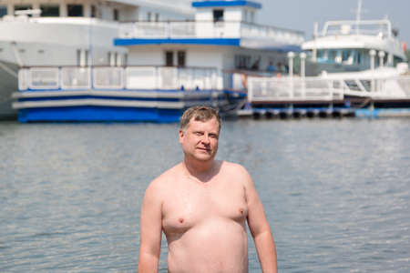 young oligarch swims in the sea against the background of his own yacht.