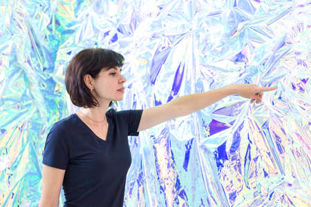 A brunette woman points in surprise with her finger against the background of an ice wall.