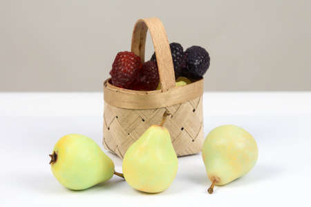 Handmade soap in form of berries and pears in a wicker basket on  white background. 版權商用圖片