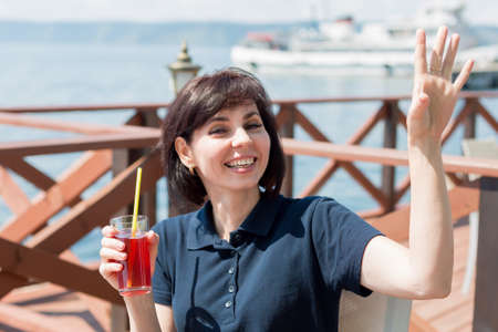 A brunette in a cafe by the sea with a glass of juice happily waves to waiter. 版權商用圖片