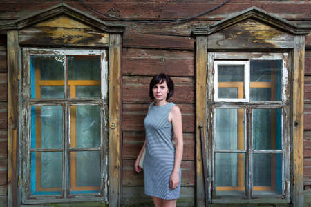 A brunette woman stands in an old wooden abandoned building.