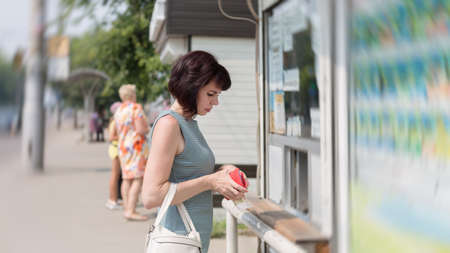 brunette on the street with a red wallet in her hand is buying ice cream at kiosk.