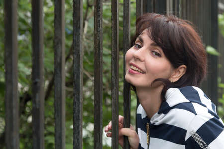 Portrait of an adult woman near iron bars of the fence.