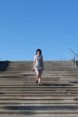 A woman striped dress quickly descends a wide staircase in the city.
