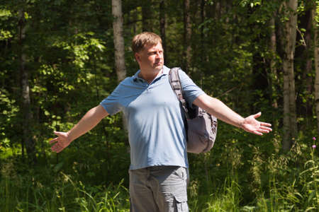 A hitchhiker tourist with a backpack on his shoulder throws up his hands in surprise on an empty road against the background of a forest. 版權商用圖片