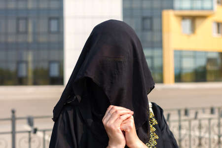 Portrait of a Muslim woman in national clothes covering her face in a European city.