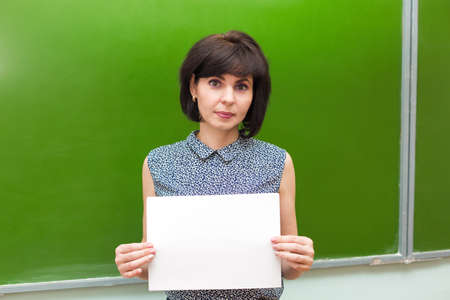 A teacher stands at the blackboard in a school classroom with a white piece of paper.