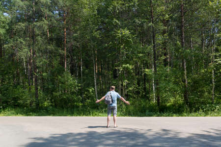 A hitchhiker tourist with a backpack on his shoulder throws up his hands in surprise on empty road against the background of forest.