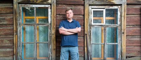 An adult man stands at a wooden abandoned building.