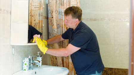 An adult man in yellow rubber gloves is cleaning the bathroom. 版權商用圖片