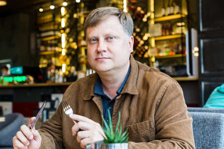 An adult blond man is having lunch in a cafe in a brown jacket.