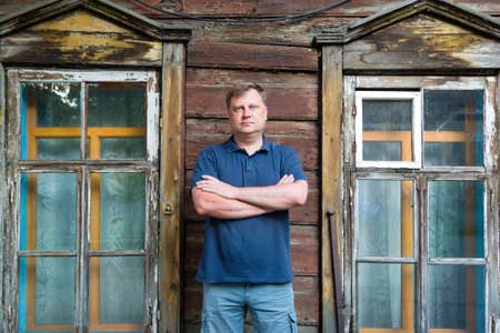 An adult man stands at wooden abandoned building.