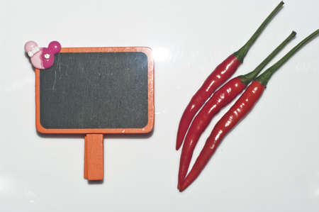 Blackboard for note and chili on the white background  photo