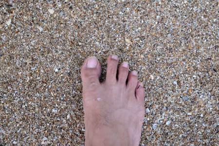 One Feet Standing In Sand Stock Photo