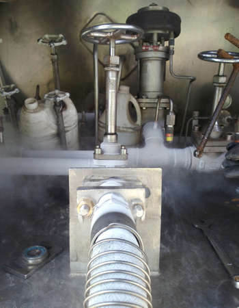 Cold metal pipe smoking from transferring liquid nitrogen Stock Photo