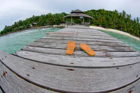 swimming shoes: shoes on the wood bridge and beach background