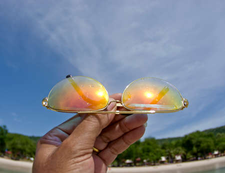 Hand holding colorful sunglasses against and blue sunny sky Stock Photo