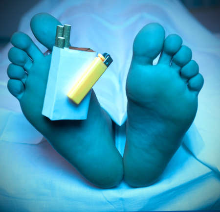 Cigarette packet and lighter using for toe tag on dead man feet under cold blue morgue light