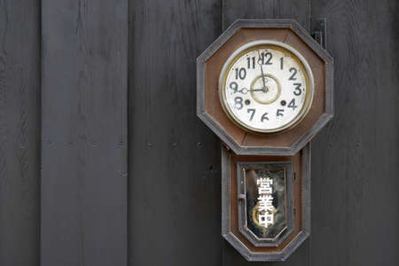 Old clock on the wood wall (foreigner word mean working hour)