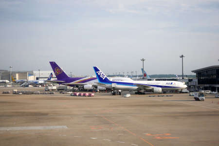 docked: NARITA, JAPAN - MARCH 4th, 2016: Thai Airways International and All Nippon Airways docked in Narita Airport. Narita Airport is a major international airport located in Chiba
