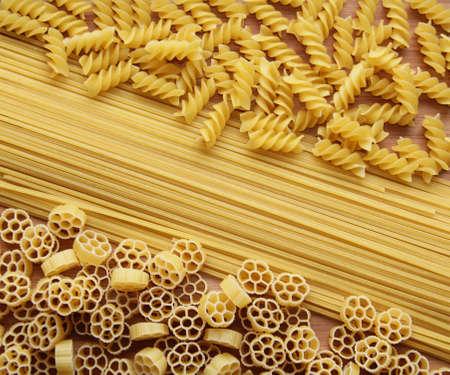 Three types of uncooked  raw  pasta  macaroni   spaghetti, fusilli and fiori photo
