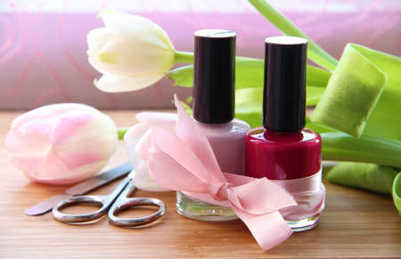 A set of manicure appliances  nail scissors, nail file and two shades of shiny nail polish with pretty tulips on the side Stock Photo - 13600483