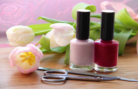 A set of manicure appliances  nail scissors, nail file and two shades of shiny nail polish with pretty tulips on the side photo