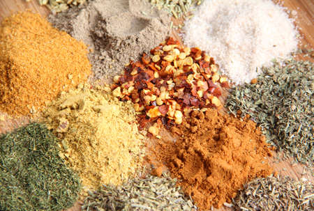 An assortment of various spices including crushed chillies, paprika, thyme and others photo