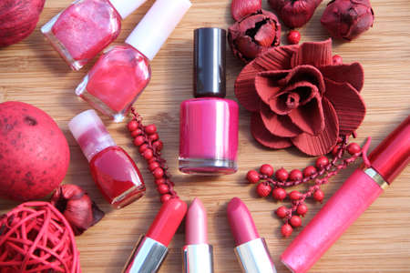 A collection of makeup  lipsticks, lipgloss and nail polishes decorated with red potpourri all in red and pink shades photo