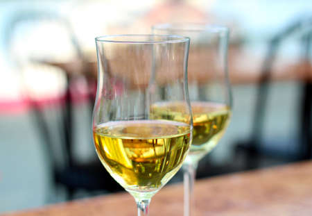Two glasses full of white wine close up against a background of a romantic cafe terrace photo