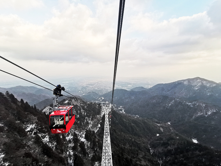 Mt.Gozaisho, JAPAN - January 23, 2019: Ropeway Lifts Red cable car pass through lot of trees in winter 写真素材