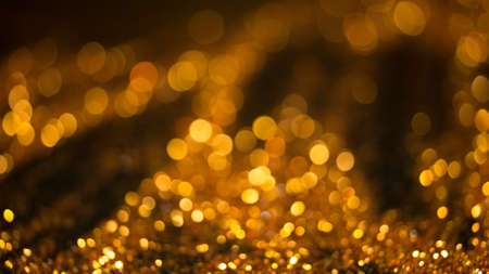 Golden lights bokeh defocus abstract background. Gold Festive Christmas. Glitter twinkled bright background. Stock Photo