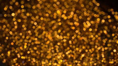 defocus: Golden lights bokeh defocus abstract background. Gold Festive Christmas. Glitter twinkled bright background. Stock Photo
