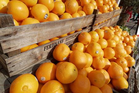 Fresh succulent oranges on wooden shelves in a market Stok Fotoğraf