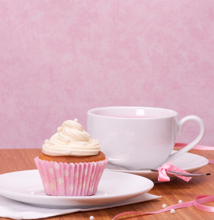 Cupcake And Fruit Tea Cup On Wooden Background photo