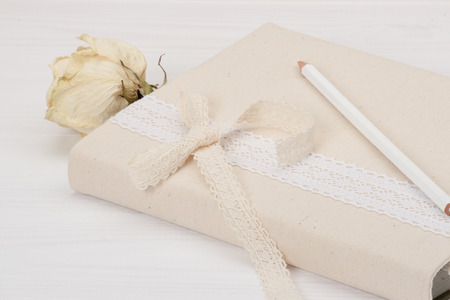 Notebook With Natural Linen Cover. Dried Rose. White Wooden Background photo