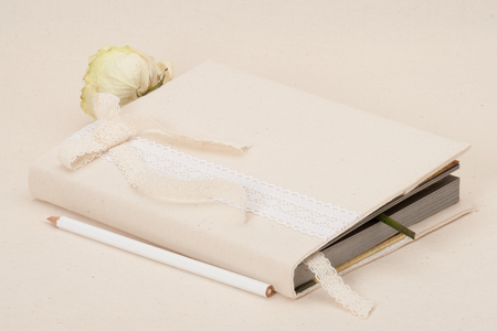 Notebook With Natural Linen Cover. Dried Rose. Fabric Background photo