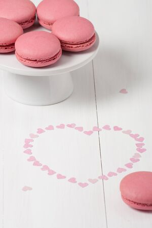a jar stand: Macaroons Biscuits On White Stand. Paper Hearts.