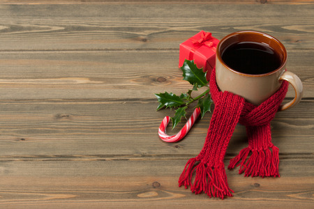 Mug Of Hot Tea Or Coffee With Scarf. Christmas Decorations. Space for Text. Wooden Background.