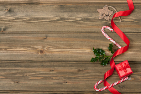 a cane: Christmas Decorations. Gift Box. Holy Leaf. Candy Cane. Space for Text. Wooden Background.