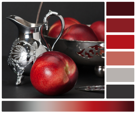 complimentary: Nectarines In Silver Basket. Old Silver Pitcher With Decorative Stamping Pattern. Palette With Complimentary Colour Swatches. Stock Photo