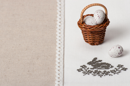 basket embroidery: Little Braided Wooden Basket With Chocolate Eggs On Handmade Natural Linen Napkin With Embroidery. Easter Theme.