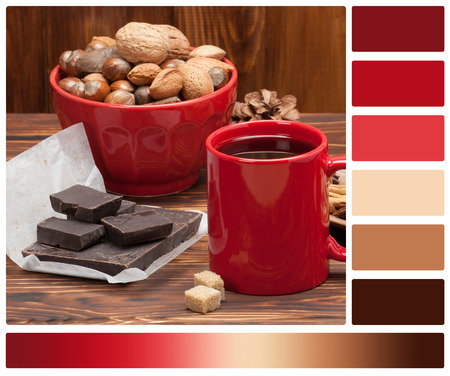 complimentary: Mug Of Tea Or Coffee. Sweets And Spices. Bowl Of Nuts. Christmas Decorations. Wooden Background. Palette With Complimentary Colour Swatches.