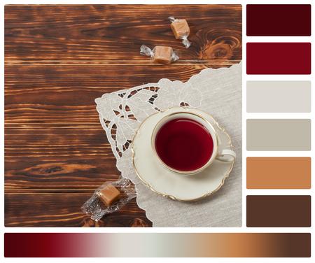 paleta de caramelo: Taza de té y placa de hueso de la multa China. Dulces. Fondo de madera quemada. Servilleta de lino natural. Con la paleta Muestras de color de cortesía.