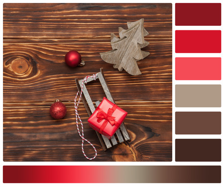 complimentary: Christmas Decorations. Gift Box On Sleigh. Wooden Background. Palette With Complimentary Colour Swatches.