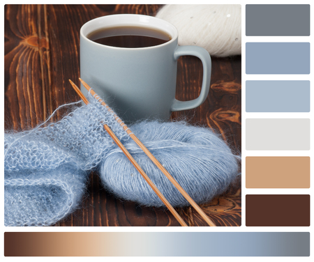 complimentary: Yarn Balls. Knit Needles. Mug Of Tea. Wooden Table. Palette With Complimentary Colour Swatches.